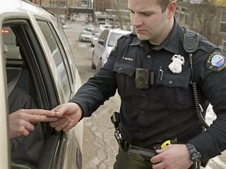 In this Feb. 2, 2015 photo, a red light on the body camera worn on Duluth, Minn. police officer Dan Merseth's uniform indicates it is active during a traffic stop in Duluth. The the city's 110 officer-worn cameras are generating 8,000 to 10,000 videos per month that are kept for at least 30 days and in many cases longer, says Police Chief Gordon Ramsay. (AP Photo/Jim Mone)